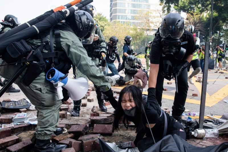 香港理工大學內示威者及學生遭警方包圍進入第3夜,數十位中學校長今(18)日晚間前往理大支援學生。圖為稍早理大內學生及示威者為突破包圍,遭警方壓制逮捕。(彭博)