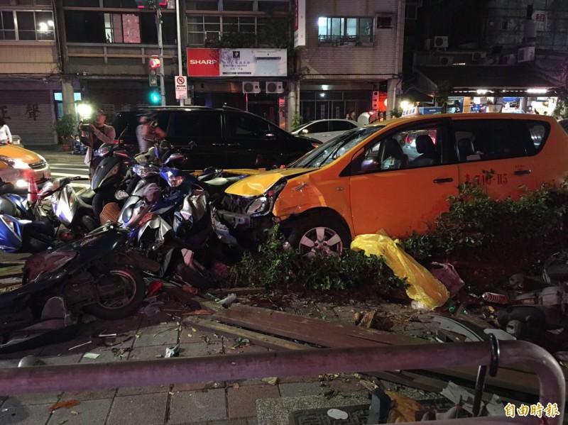 台北市吉林國小前今日下午一輛計程車不明原因突然衝撞人行道上,把路旁機車撞成一團。(即時新聞組攝)