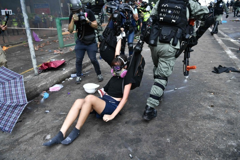 示威民眾下午企圖突圍,與警再度爆發嚴重衝突,多人受傷遭壓制,有女示威者直接遭港警拖行帶走。(法新社)