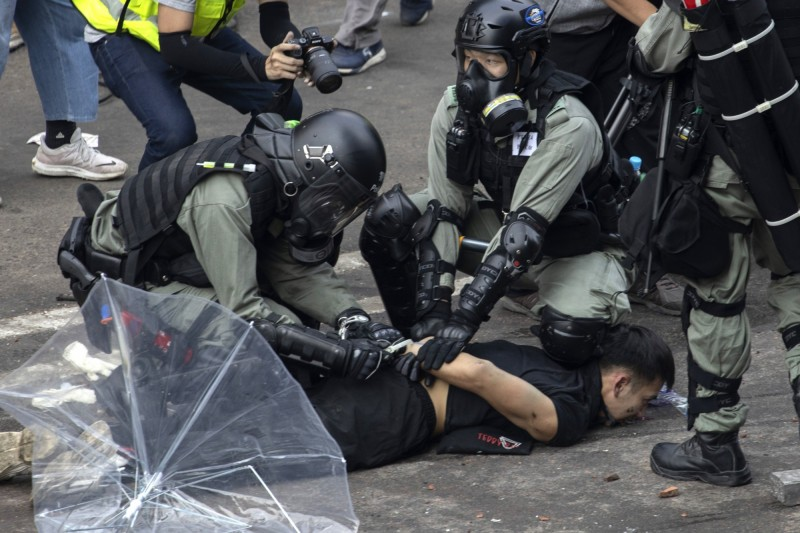 突围者遭优势警力镇压,许多人头部挂彩遭警压制。(美联社)