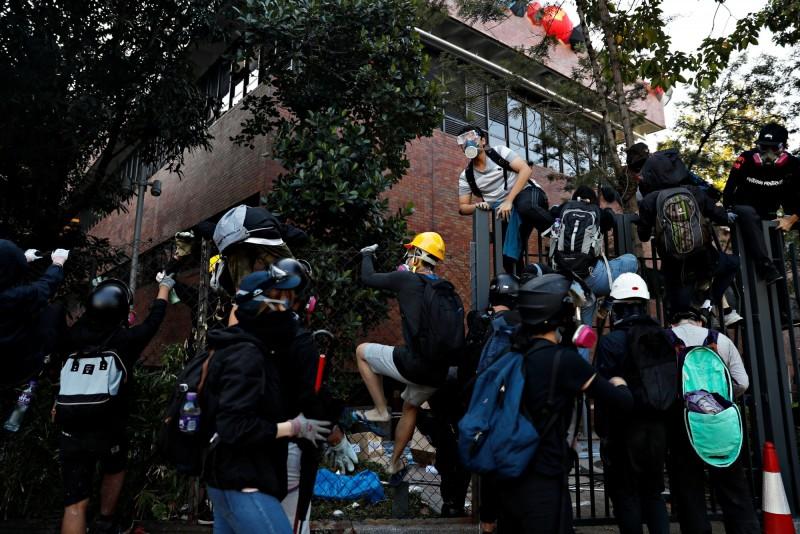 一批示威者從理大突圍,試圖爬鐵柵欄離開。(路透)