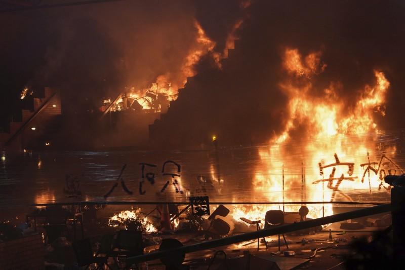 警方於凌晨突擊理大正門,於門口制服多名黑衣人,並嘗試攻入噴水池,有示威者見狀丟擲燃燒彈,現場陷入一片火海。(美聯社)