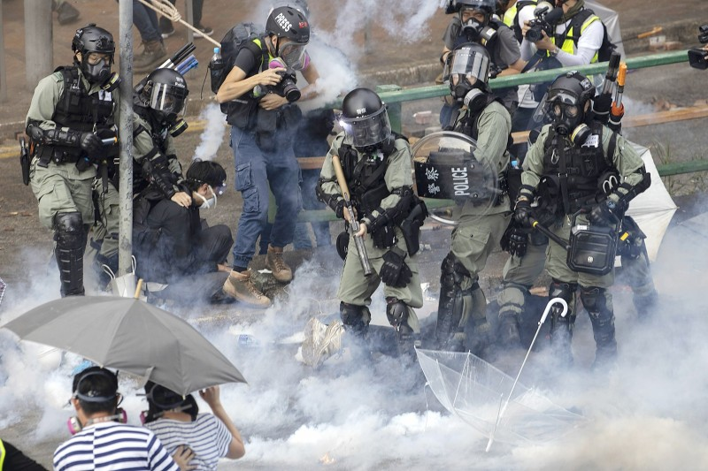 Riot police detain protesters yesteray amid clouds of tear gas at the Hong Kong Polytechnic University in Kowloon. Photo: AP