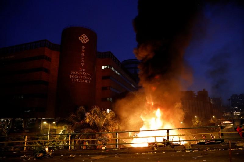 大批防暴警察及「速龍小隊」今晨從暢運道攻入理工大學,有示威者點燃原本的路障,現場頓成一片火海,示威者則陸續退入校園內。(路透)