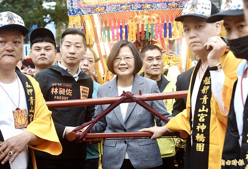 President Tsai Ing-wen, center, and independent Legislator Freddy Lim, left, help carry a palanquin at Cingshan Temple in Taipei's Wanhua District yesterday. Photo: Chien Jung-fong, Taipei Times