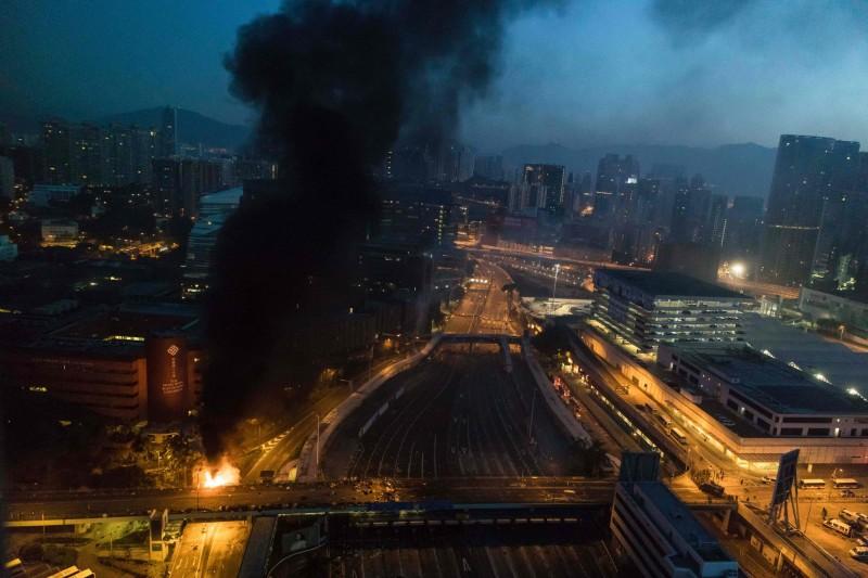 警方於凌晨突擊理大正門,於門口制服多名黑衣人,並嘗試攻入噴水池,有示威者見狀丟擲燃燒彈,現場陷入一片火海。(法新社)