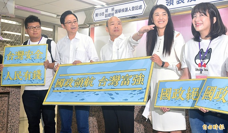 Kaohsiung Mayor Han Kuo-yu, the Chinese Nationalist Party's (KMT) presidential candidate, center, and his running mate, former premier Simon Chang, second left, hold placards after registering at the Central Election Commission in Taipei yesterday for the Jan. 11 presidential election. Photo: Liao Chen-huei, Taipei Times