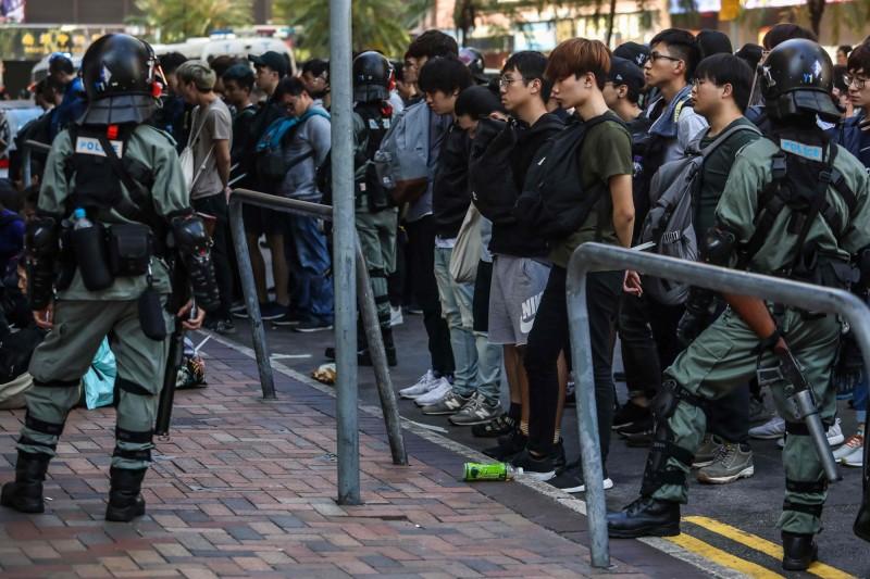 港警持續包圍理大,有百名市民試圖前往支援,卻遭鎮暴警察包抄,至少60人被捕。(法新社)