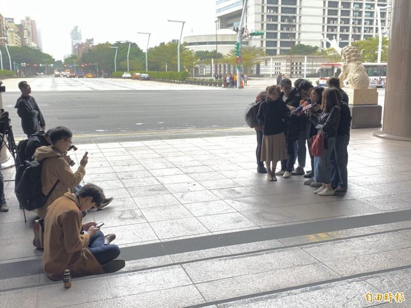 劉姓記者為避嫌,後來請同業幫忙拿麥克風,自己則坐在遠方,埋頭滑手機裝低調。(記者沈佩瑤攝)