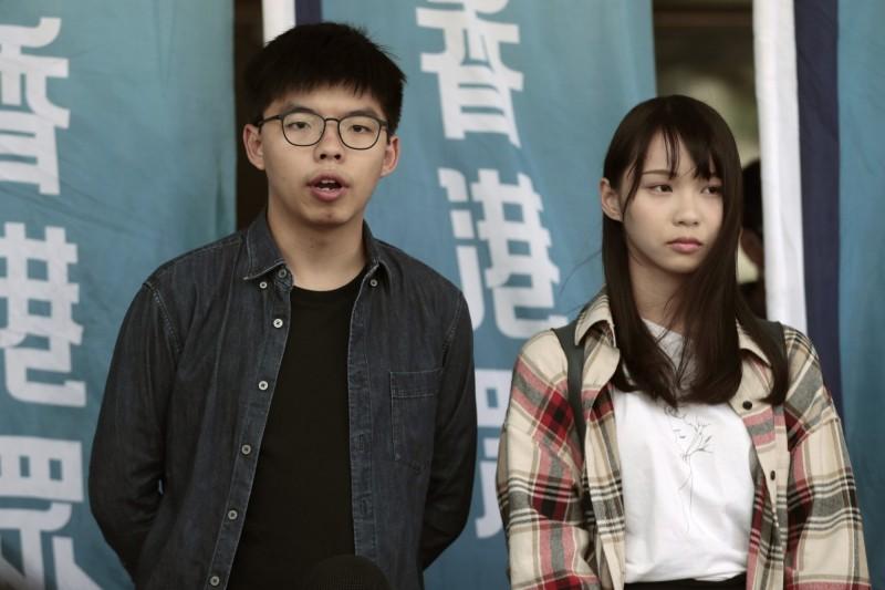 香港眾志秘書長黃之鋒(左)因遭控以政治罪「未經批准集結」,離港申請遭港高院否決,獲邀至歐洲6國「開花」的行程被迫取消。(美聯社)
