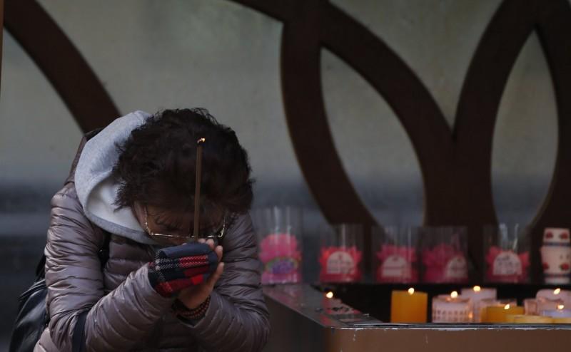 每當南韓發生重大事件時,密陽市弘濟寺內表忠碑,就會不停「流汗」,最近這塊神秘石碑再次「大汗淋漓」,引起熱議。圖為南韓民眾到廟裡上香祈福。(資料照,歐新社)