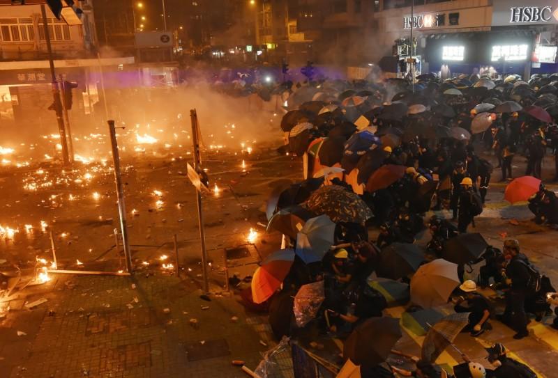 示威群眾以傘陣及丟擲汽油彈對抗港警。(歐新社)