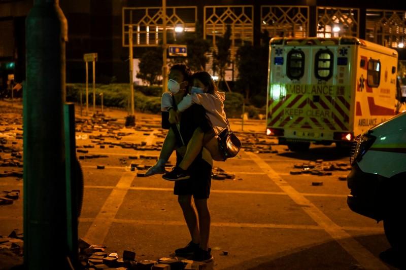 香港理工大學淪為戰場,連日爆發警察與學生激烈衝突。圖為一名年輕男子將女示威者送往救護車上。(法新社)