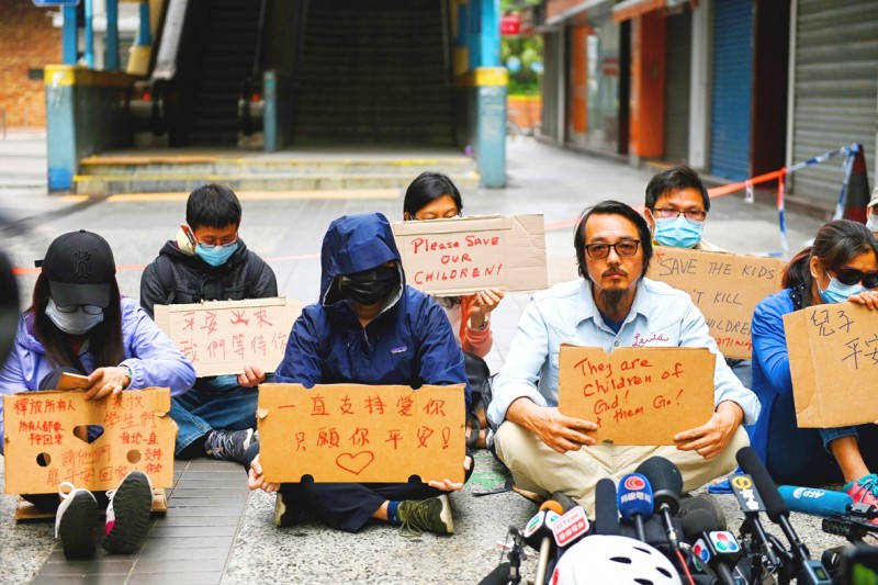 Family members of students barricaded inside Hong Kong Polytechnic University hold up signs during a protest near the university in Hung Hom yesterday. Photo: AFP