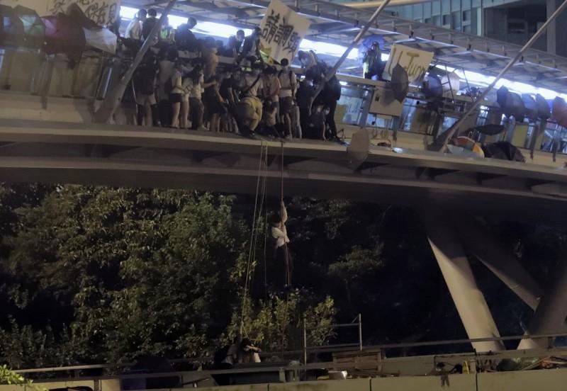 示威者嘗試從行人天橋垂降到橋面道路上。(美聯社)