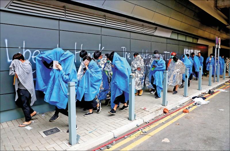 部分示威者撤出校園時裹著毛毯、錫箔紙保暖。(路透)