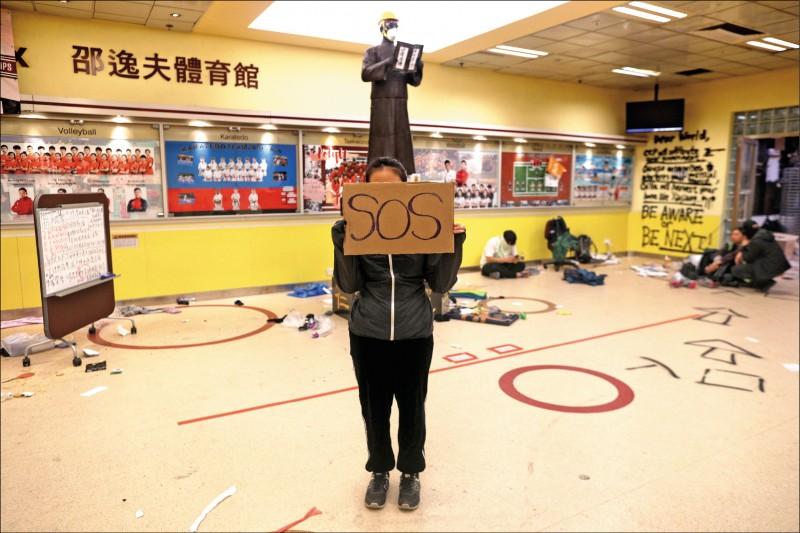 續留守理大的示威者舉起求救看板,盼外界伸出援手。(歐新社)