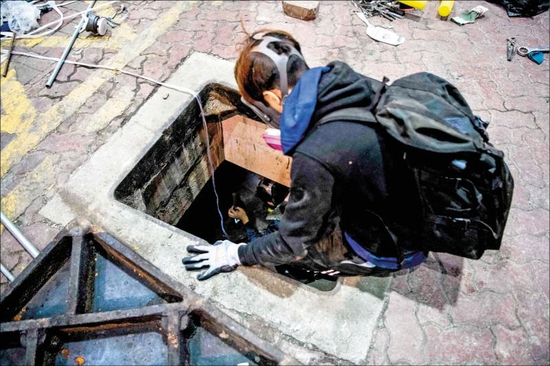 一名示威者試圖爬下下水道逃脫。(法新社)