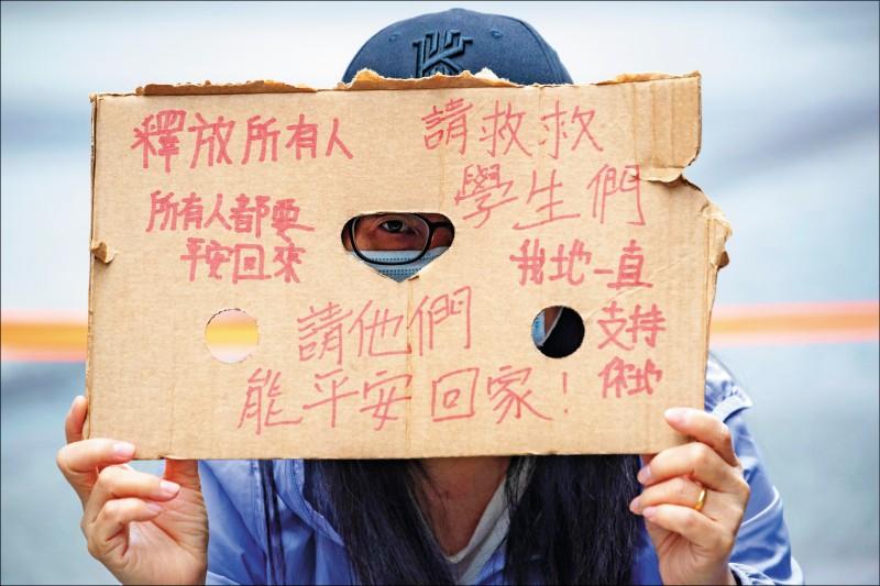 理大外徹夜守候的家長,舉著破舊的手寫紙板,盼望孩子平安歸來。(美聯社)