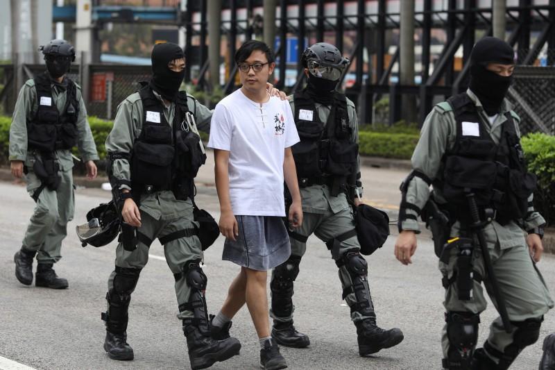 香港傳出學生上學時遭警察攔檢甚至用警車載走,港府教育局長楊潤雄表示警方這麼做一定有理由。圖為港警在理大附近逮捕示威民眾。(歐新社)