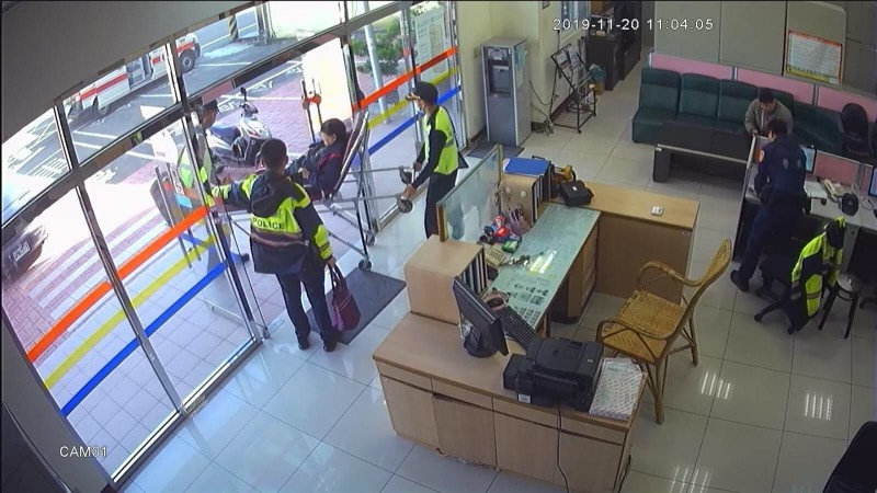 竹東分局二重埔派出所員警楊昱彥將被機車壓傷的婦人揹返警所稍作休息,奉上熱茶並通知救護車將她送醫救治。 (記者廖雪茹翻攝)