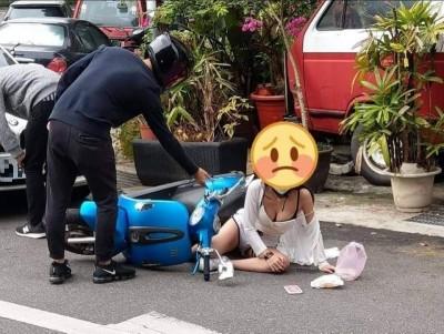 一名身材姣好、衣著性感的女子在路上發生交通擦撞後跌坐在地的照片,引起眾多網友湧入留言關心。(圖擷取自臉書_爆廢公社)