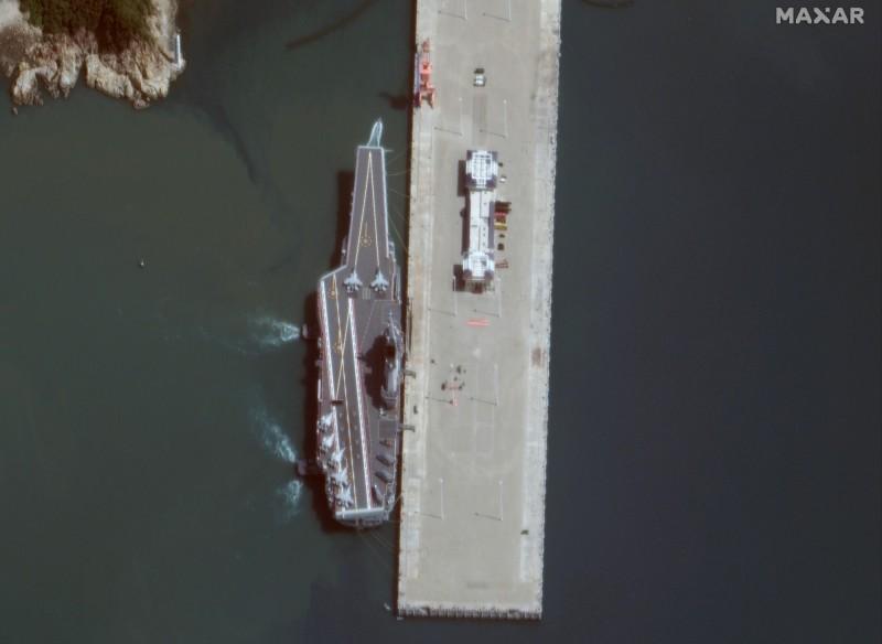衛星中國自製航艦「002」的最新畫面,停留在三亞榆林軍港「002」,其甲板上已出現至少7架「殲-15」及4架直升機。(美聯社)