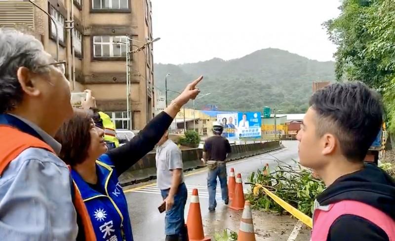 國民黨立委參選人宋瑋莉(左二)、基隆市議員林旻勳(右)與市府工務處人員,正在討論如何處理,不讓土石繼續滑落。(記者俞肇福翻攝)