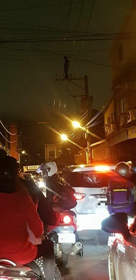 梁姓男子一度爬到電線桿頂,嚇壞路過的人車。(取材自臉書社團「桃園人桃園事」)