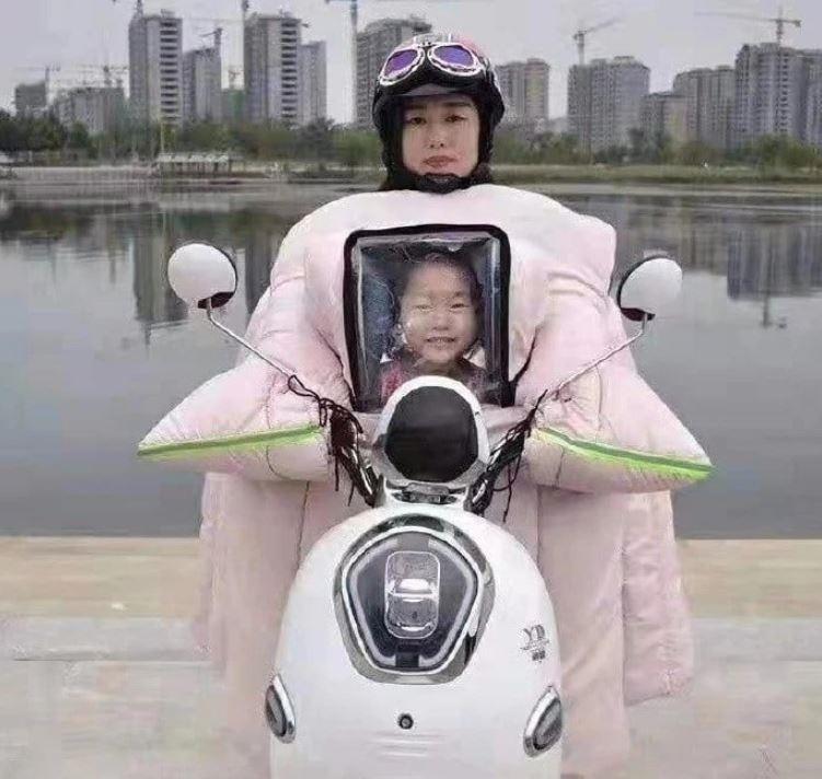 淘寶近日推出「母子款」騎車擋風禦寒被,但設計似乎太過奇葩,使用起來竟像是「母捧子遺照」,照片笑翻日本網友。(圖擷取自@harakoatom推特)