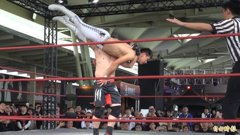 職業摔角表演賽熱血登場,吸引不少民眾圍觀拍照。(記者余家緯攝)