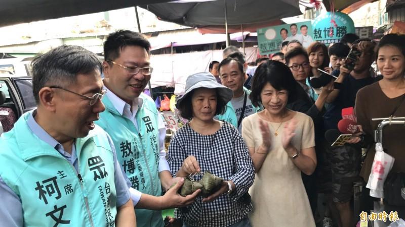 柯文哲夫妻走進市場輔選,攤商送敖博勝(左2)粽子祝福「包中」。(記者洪臣宏攝)