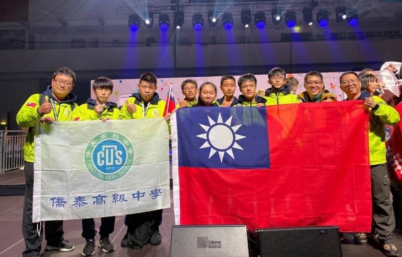僑泰高中資訊科吳育丞(左2)、張睿承(左3)在教練徐炳辰(左1)指導下拿下國際奧林匹亞機器人大賽世界第3,開心拿著國旗上台領獎。(記者陳建志翻攝)
