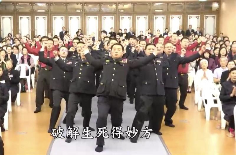 引領隊伍手舞足蹈宣揚佛法的男子,被查出是任職中央警察大學的三線一星徐姓組長(中)。(記者魏瑾筠翻攝)