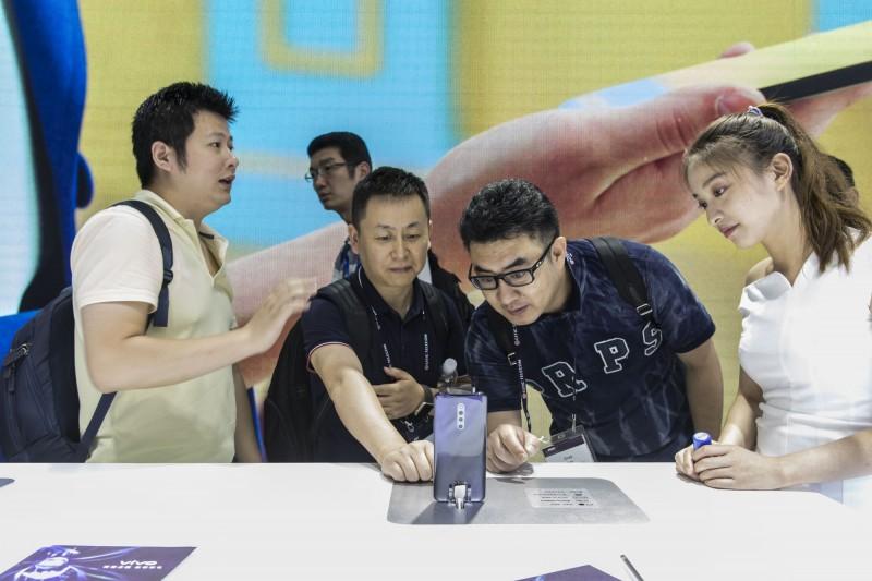 中國規定民眾註冊新手機時都需要掃描臉部,宣稱這是為了要保護「公民在網路空間中的合法權益」。圖為上海世界行動通訊大會上,民眾在Vivo攤位試用手機。(彭博)