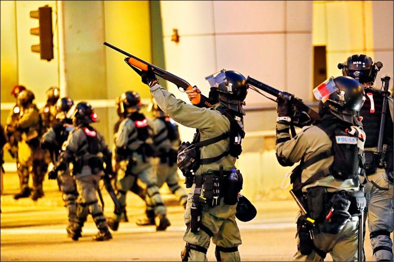 鎮暴警察持槍與示威者對峙。(美聯社)
