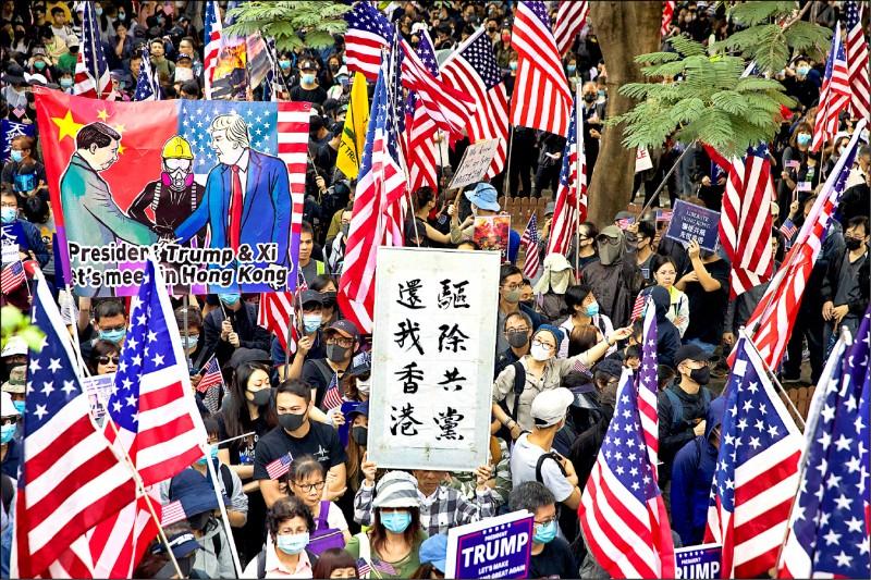 參加「感謝美國保護香港」遊行的民眾,高舉美國國旗與「驅逐共黨,還我香港」標語。(美聯社)