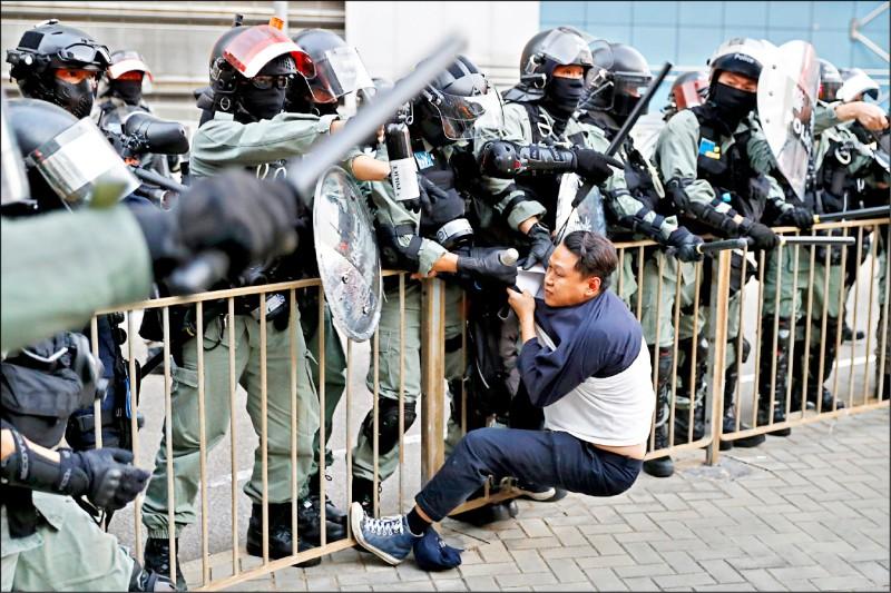 一名男性示威者遭鎮暴警察拘捕。(美聯社)