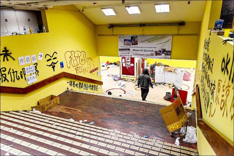 在香港警方圍困理工大學期間堅守不退的「麥可」。圖為麥可十一月廿六日晚間正要去沖澡,牆上可見許多「反送中」相關塗鴉和文字。(法新社)