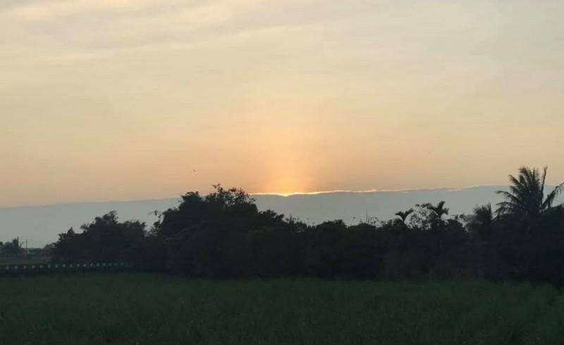 太陽躲入如一條線後的雲層。(讀者提供)