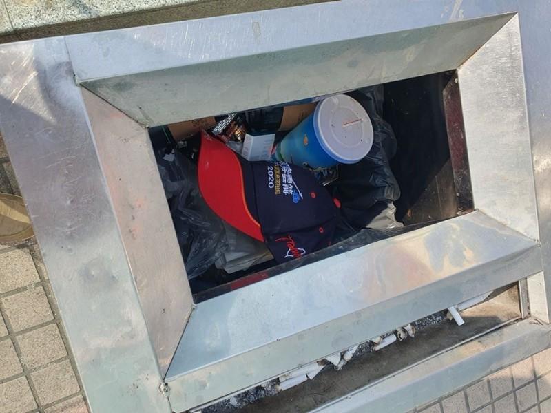 高雄市民發現,韓粉出席造勢場合配戴的帽子,出現在路邊垃圾桶裡。(圖取自公民割草行動)