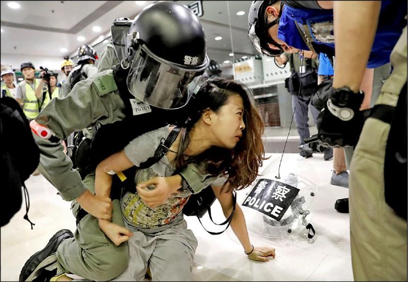 香港近來局勢不穩,港人申請來台居留人數增加。圖為港警上月在一間位於大浦的賣場內壓制一名女子。(路透檔案照)