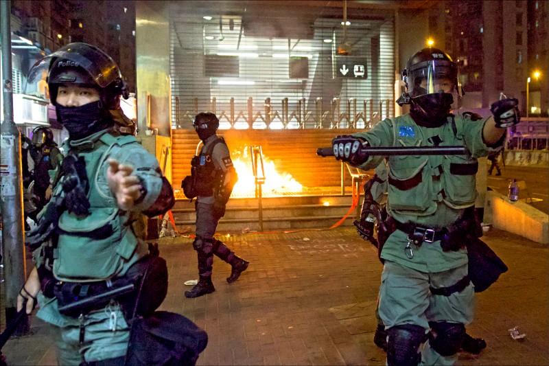 反送中示威者1日在港鐵黃埔站入口處縱火,鎮暴警察趕到後在現場佈防警戒,阻止示威者闖入破壞設施。(美聯社)