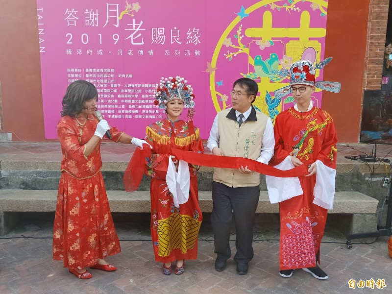 市長黃偉哲扮演好命公,為新人牽起象徵幸福的紅線。(記者王姝琇攝)