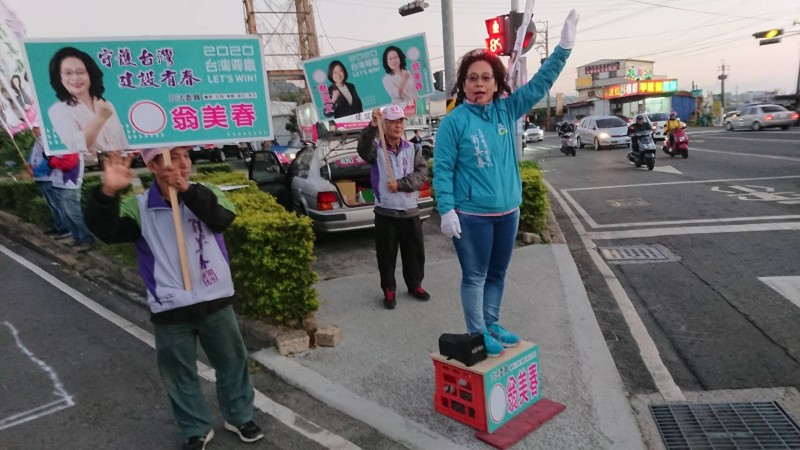 翁美春站路口自備箱子墊高,讓選民看得更清楚。(翁美香服務處提供)
