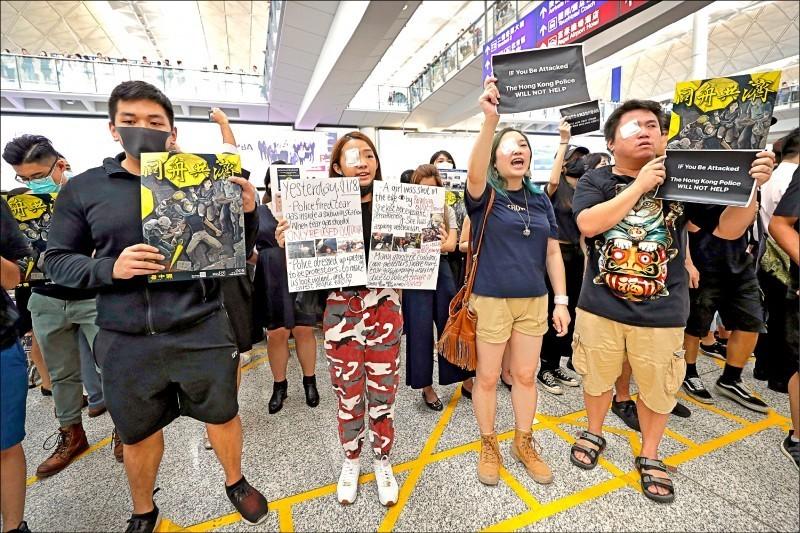 示威者以紗布遮住右眼,聲援遭警方近距離射爆眼球的女子,並透過標語向外來旅客解釋來龍去脈。(美聯社)