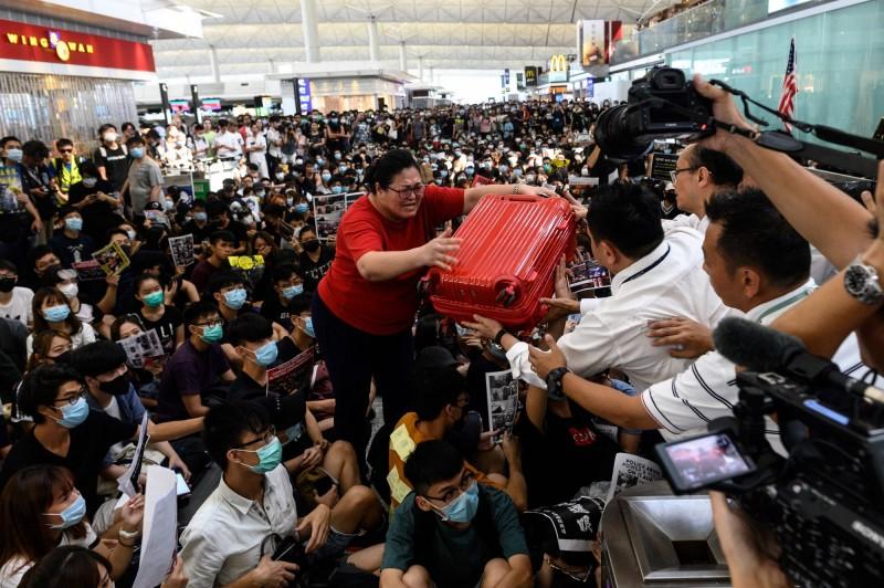 8月11日晚間警方強力鎮壓「反送中」遊行,一名女急救員疑似被布袋彈射中眼睛,可能毀容及永久失明。港民於8月13日癱瘓香港機場,旅客無法經1號客運大樓前往離境大廳。(法新社)