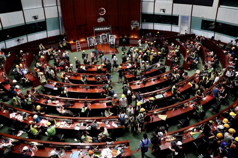 7月1日適逢香港主權移交22週年,聚集在立法會大樓周邊抗議《逃犯條例》的示威者,有部分人在晚間衝入立法會內部,佔領立法會會議廳,並於室內塗鴉、拆卸立法會現任及前任主席圖片。(路透)