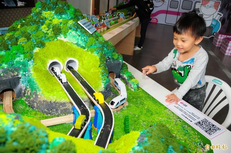 「阿嬤我看到火車跑過來了」!火車嘟嘟過山洞的畫面讓孩子笑開懷,蕭美琴競選總部用火車模型介紹政績,小孩子們完全被吸引,家長也頗開心。(記者花孟璟攝)