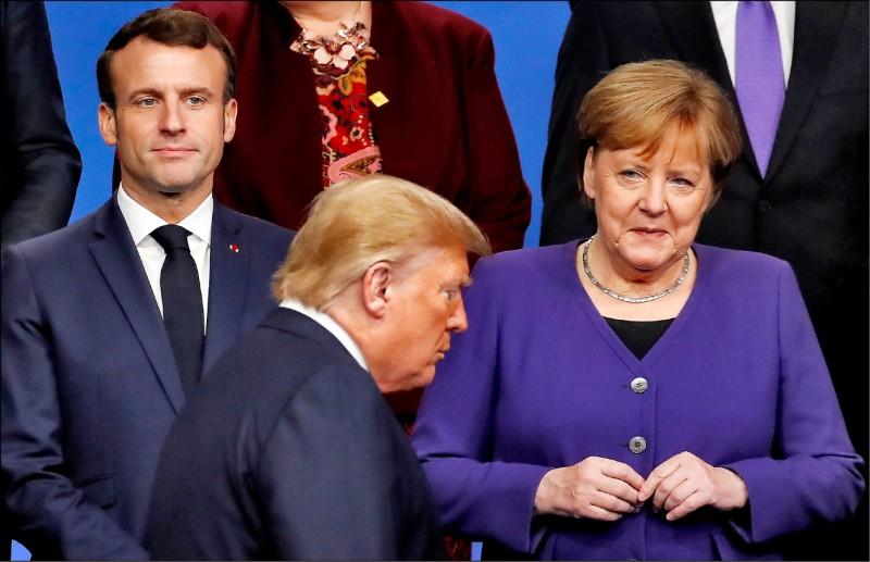 美國總統川普(圖中)四日準備在北約峰會合照時,走過法國總統馬克宏和德國總理梅克爾面前。(路透)